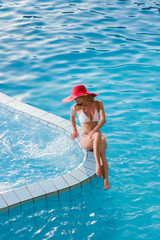 woman wearing a red hat sitting in the pool
