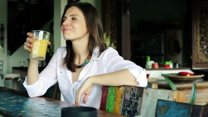 Beautiful woman drinking juice by the table at home