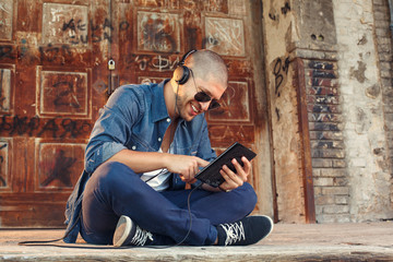 handsome young man listening to music with headphones via tablet