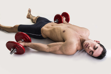 Exhausted young male bodybuilder resting on floor