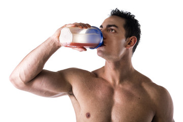 Muscular shirtless male bodybuilder drinking protein shake