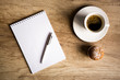 Empty paper with cup of coffee on wooden table
