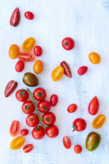 Variety of tomatoes on white rustic background