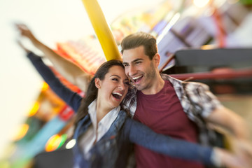 Laughing couple enjoy in riding ferris wheel