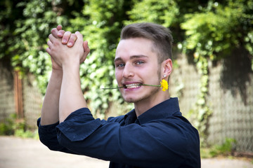Handsome young man with flower in mouth clapping