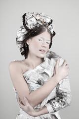 Портрет девушки в головном уборе и платье из газет