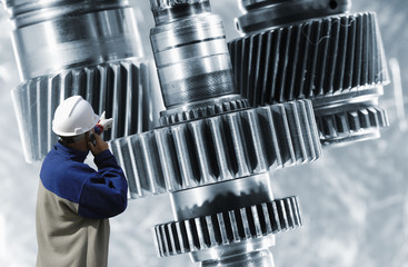 engineer pointing at large gears and axles, technology
