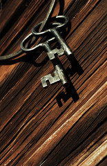 old keys and ring against wooden wall