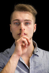 Attractive young man gesturing Hush or Silence