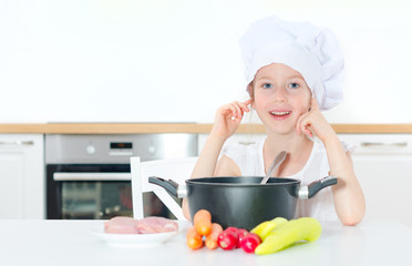 Little girl in chef hat cooking in kitchen.