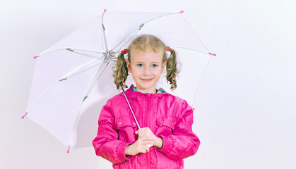Little girl in bright coat holding umbrella. Indoors.