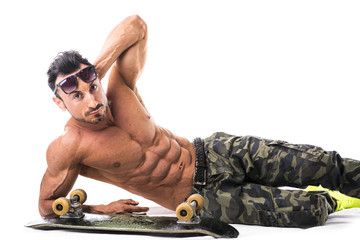 Shirtless muscular man on the floor with skateboard
