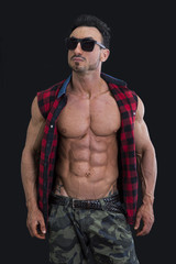 Male bodybuilder with shirt open on naked muscular torso