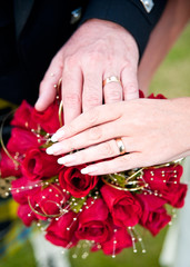 Senior Couple Holding Hands over a wedding red rose bouquet