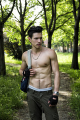 Young man shirtless outdoors hiking with backpack on shoulder
