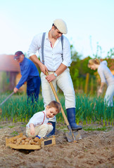 family planting potatoes in vegetable garden