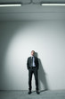 Businessman leaning on a wall