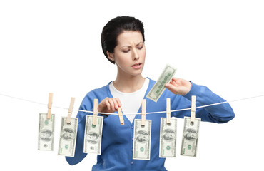 Woman hangs currency on the line with clothespins