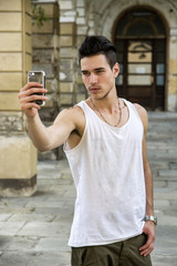 "Young man smiling and taking ""selfie"" with cell phone's camera"