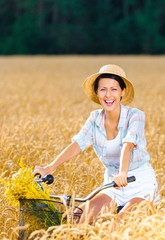 Girl pedals cycle with flowers in rye field