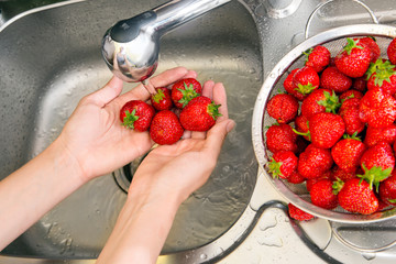 girl washes strawberries