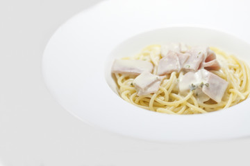 spaghetti with cream sauce on a white background