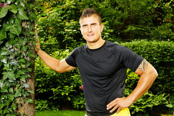 Young man in sportswear leaning on a tree