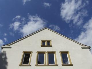 Fassade mit Fenstern und spitzem Giebel vor Wolkenhimmel
