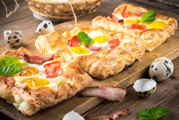 Pie of quail eggs with tomato and bacon