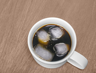 Cold iced black coffee,white ceramic mug,wood grain background