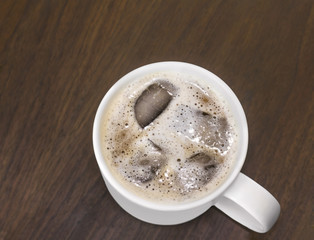 Cold iced coffee with milk foam in white ceramic mug
