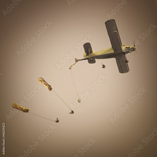 Retro style picture of the biplane with skydivers. - 66265623