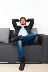 man sitting on sofa living room guy hipster