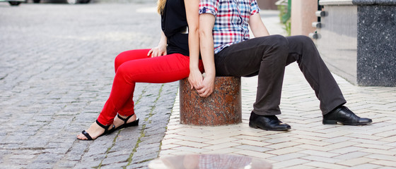 Love couple sitting on the pavement