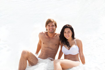 Couple on beach, sitting in water wave foam sea
