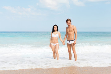 Couple on beach standing in water wave foam