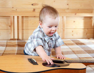 Happy toddler playing guitar