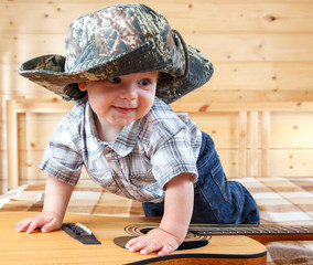 Cute baby in cowboy hat climbing the guitar