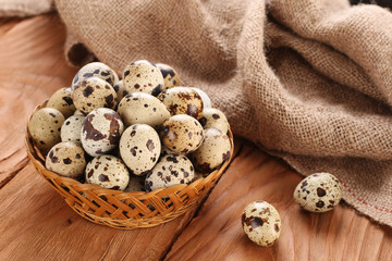 quail eggs in a wicker basket on the background of wooden planks