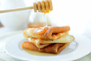 Three pancakes with butter and honey