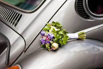 Wedding bouquet on old fashioned car.