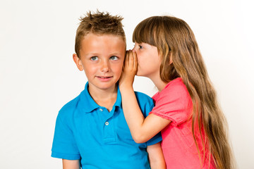 Girl whispering to boy