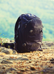 black tourist backpack on nature