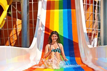 Woman in bikini sliding water park.