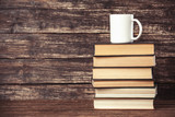 Fototapety Books and cup of coffee on wooden background.