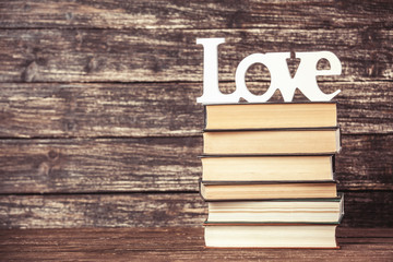 Word love and books on wooden table.