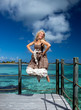 beautiful woman jumps up on wooden platform over sea