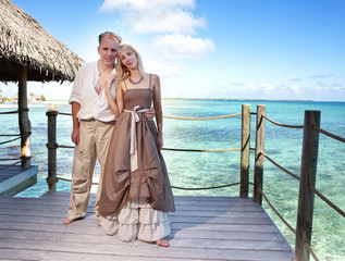 Loving couple on a wooden platform over sea on tropical island