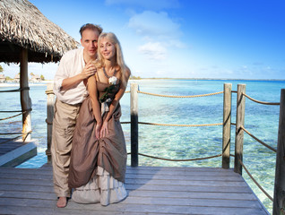 Loving couple on a wooden platform over sea on tropical island..