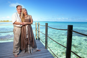 Loving couple on wooden platform over sea on tropical island..